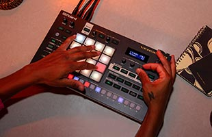 top view of Roland Verselab MV-1 sitting on table being operated by musician's hands