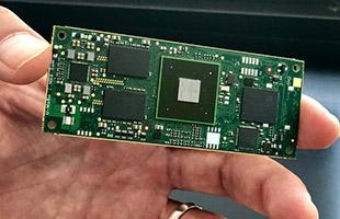 closeup image of hand holding quad-core processor chip