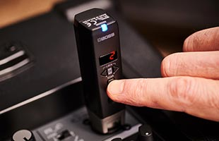 close-up view of Boss WL-30XLR installed in portable powered speaker with user's finger making adjustments