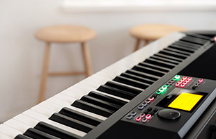 image with closeup of Korg XE20 keybed in foreground and two wooden stools in background