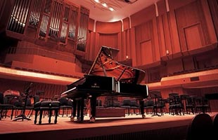 Yamaha concert grand piano on stage in concert hall