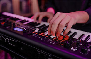 close-up image of musician's hands playing Yamaha YC73 on stage