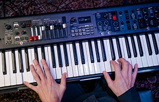 overhead view of musician's hands playing Yamaha YC73