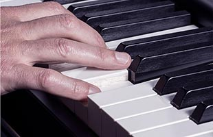 detail image of musician hands playing Yamaha YC88 showing natural wood keys