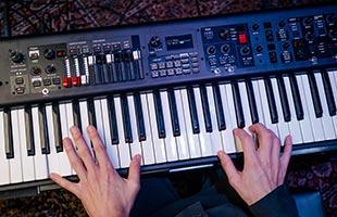 overhead view of musician's hands playing Yamaha YC88